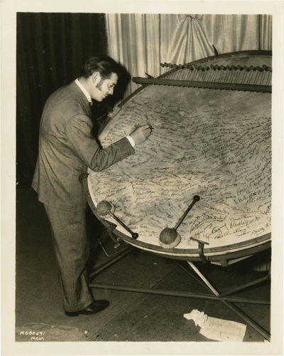 1940 photo of Clark Gable signing the world's most valuable kettle drum (not as interesting if it was the second most valuable kettle drum)