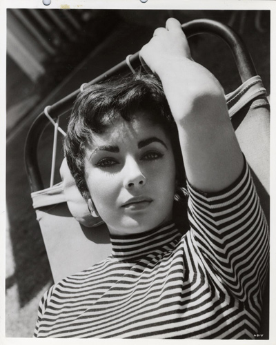 Glossy black and white photograph of a 22 year old Elizabeth Taylor taken during her most stylized 1950s period. Photograph taken August 25 1954.