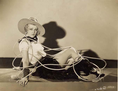 A publicity photo still from an early M.G.M. sound musical featuring a reclining chorus girl in cowgirl costume with a lasso around her, 1929.
