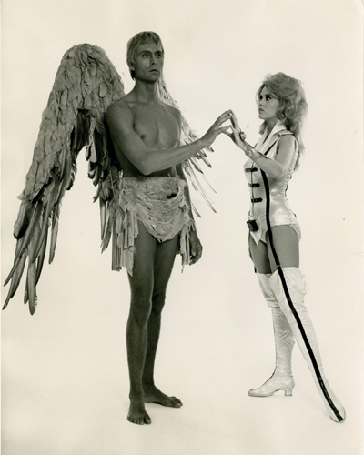 Vintage borderless black-and-white single weight studio still photograph from the Italian release of the 1968 film. Jane Fonda, in full regalia, stands next to her angel, Pygar (John Philip Law).