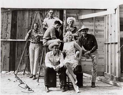 Staged photo of the stars and crew of The Misfits including Marilyn Monroe, Arthur Miller and Clark Gable. Signed by Arthur Miller.