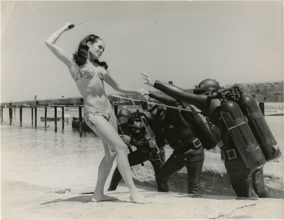 A candid, humorous photograph from Thunderball in which Bond girl Martine Beswick fends off bad guys in scuba gear.