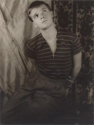 1948 photograph from one of a famous series taken by Van Vechten of the 23-year-old Capote posing in slacks and t-shirt, in front of a theatrical backdrop of marionettes