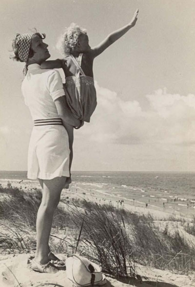 Photographed by Emil Otto Hoppe, a mother holds her child at the beach circa 1930.