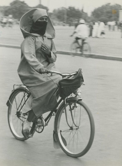 A Moroccan woman rides a bicycle.